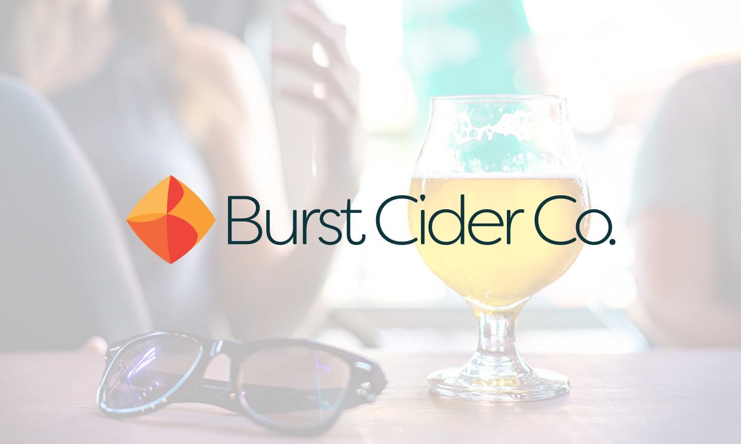 The Burst Cider Co logo overlayed on a photo of a cider poured into a glass on a table in a restaurant.