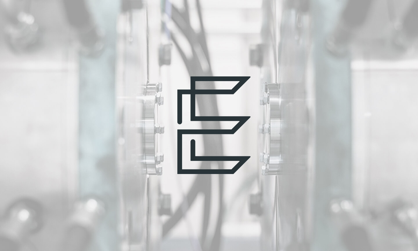 Enable Innovation Product Development company's logo overlayed on a photo of a shiny industrial fitting made of metal